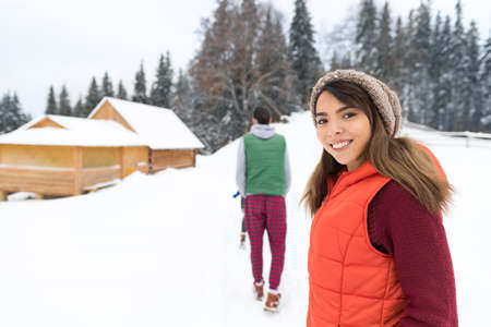 village man: Young Couple Snowy Village Wooden Country House Man And Woman Winter Snow Resort Cottage Holiday Vacation Stock Photo
