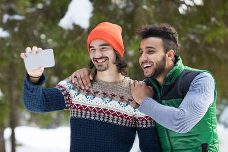 Zwei Mann halten Smartphone-Kamera unter Selfie Foto Schnee Wald Mix Rennen paar Outdoor Winter Pine Woods