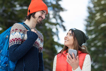 Couple Using Smart Phone Chatting Online Snow Forest Happy Smiling Man And Woman Walking Outdoor Winter Pine Woods Stock Photo