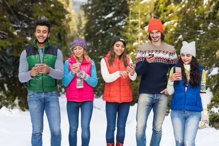People Group Using Smart Phone Chatting Online Snow Forest Happy Smiling Young Friends Walking Outdoor Winter Pine Woods