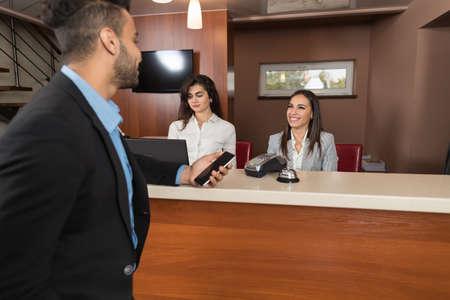 ビジネスの男性が受付カウンターで携帯電話の女性の受付登録とホテル チェックに到着します。 写真素材