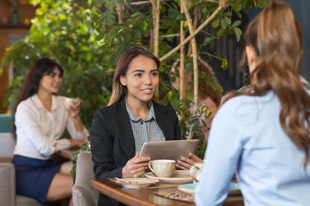 break from work: Young Business Woman Drink Coffee Sitting Cafe Table, Asian Girl Hold Tablet Computer Smiling Talking Stock Photo