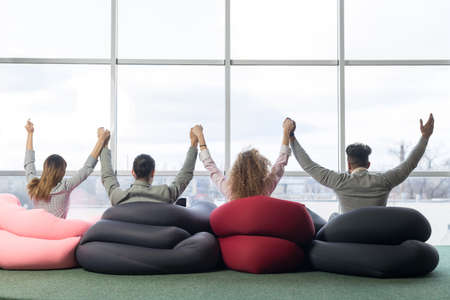 Cheerful Businesspeople Group In Coworking Center Team Coworkers Raised Hands Sitting in front Big Panoramic Window Modern Office Back Rear View