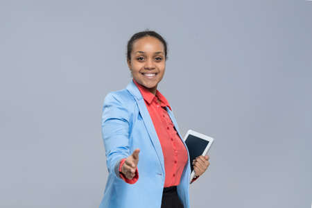 african american handshake: Young Business Woman Hold Tablet Computer African American Girl Handshake Welcome Gesture Businesswoman Isolated Over Gray Background