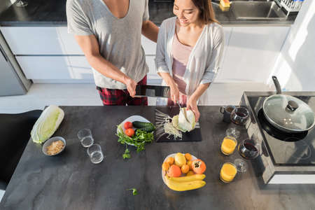 Young Couple In Kitchen, Asian Woman Cooking Food Breakfast, Hispanic Man Show Cell Smart Phone Modern Apartment Interior