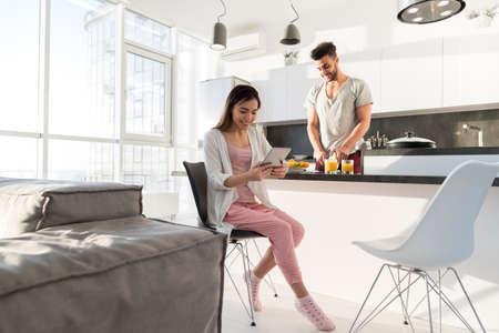 Giovane coppia prima colazione, donna asiatica utilizzando computer Tablet Uomo ispanico che cucina Cucina Interiore moderno dell'appartamento