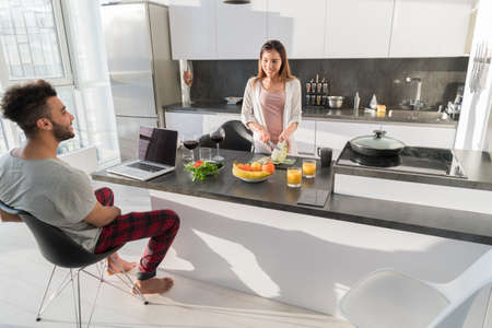 moderm: Young Couple Having Breakfast, Asian Woman Hispanic Man Cooking Food Kitchen Modern Apartment Interior Stock Photo