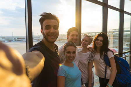Young People Group In Airport Lounge Near Windows Happy Smile Mix Race Friends Taking Selfie Photo Flight Stockfoto