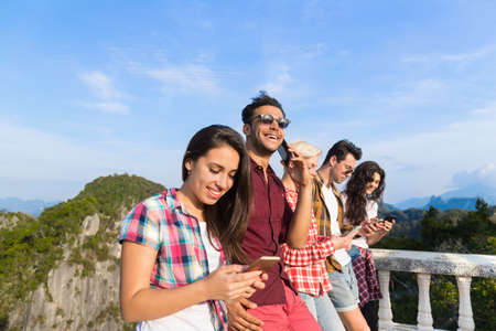 Young People Group In Mountain Using Cell Smart Phone Chatting Online Friends Asian Holiday Summer Vacation Travel Stock Photo