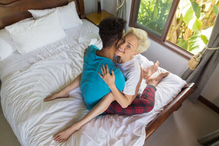happy couple in bed: Young Couple Lying On Bed, Happy Smile Hispanic Man And Woman Embrace Bedroom Hotel Room Interior