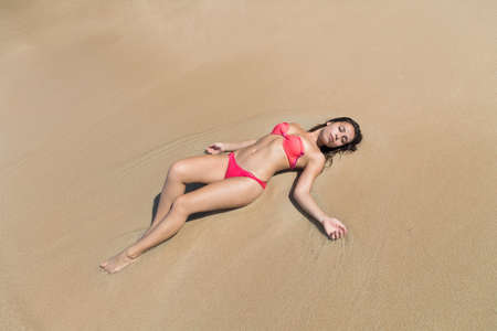 bikini top: Attractive Young Caucasian Woman In Swimsuit Lying On Beach Top View, Girl Wet Sand Sea Ocean Holiday Summer Vacation Stock Photo