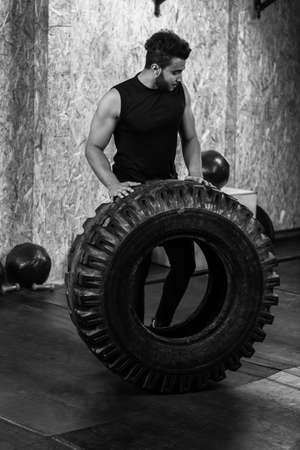 strong: Sport Fitness Man Flipping Wheel Tire Crossfit Training, Young Healthy Guy Gym Interior Stock Photo