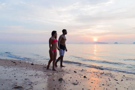 holding hands while walking: Couple Holding Hands Walking On Beach At Sunset, Young Tourist Man And Woman On Sea Holiday While Summer Vacation