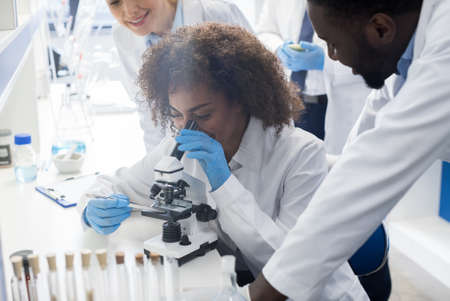 Male Scientist Working With Microscope, Team In Laboratory Doing Research, Man And Woman Making Scientific Experiments Doctors In Lab Standard-Bild