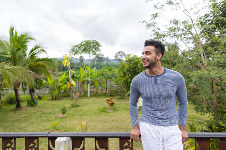 looking aside: Happy Smiling Latin Man Over Green Tropical Rain Forest Landscape, Hispanic Guy Looking Aside