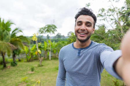 Gelukkige Glimlachende Latijnse Mens die Selfie Foto over Groen Tropisch Regenwoudlandschap op Cel Slimme Telefoon nemen