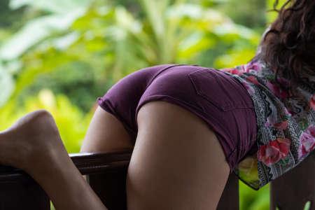 Zurück Rückansicht der Sexy Lady Wearing Shorts Closeup entspannend auf Sommer-Terrasse mit Unschärfe Green Forest Background Standard-Bild - 81019183