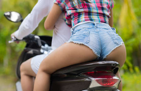 Closeup Of Couple Sitting On Motorcycle Back Rear View, Beautiful Casual Man And Woman Ride Motorbike On Road In Green Tropical Forest