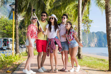 People Group Take Selfie With Action Camera On Stick While Walking In Palm Tree Park On Beach, Happy Smiling Mix Race Friends On Summer Vacation