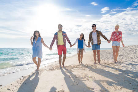 Young People Group On Beach Summer Vacation, Happy Smiling Friends Walking Seaside Sea Ocean Holiday Travel Stock Photo