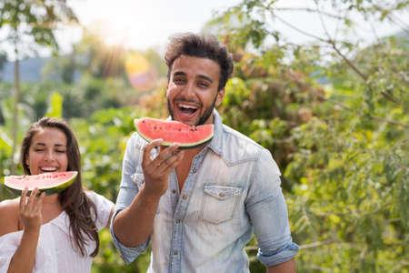 Happy Man And Woman Eating Watermelon Together Over Beautiful Tropical Forest Landscape Cheerful Couple Laugh Holding Slice Of Fresh Water Melon Outdoors Stock Photo