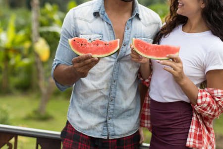 Closeup Of Young Couple Holding Watermelon Slice Embracing Together Unrecognizable Man And Woman Outdoors ON Summer Terrace Over Palm Trees Background Stock Photo