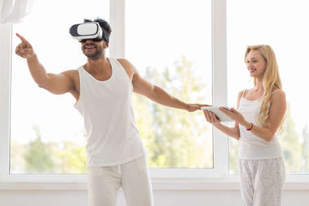 Hispanic Man Wear Virtual Reality Digital Glasses, Happy Smiling Girl Using Tablet Over Big Window Stock Photo