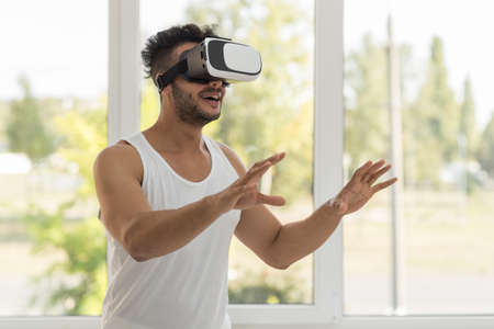 Young Hispanic Man Wear Virtual Reality Digital Glasses, Happy Smiling Guy Over Big Window Stock Photo