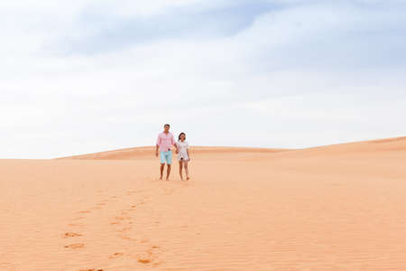 Young Man Woman Walking In Desert Couple Girl And Man Hold Hands Sand Dune Landscape Nature Background Stock Photo