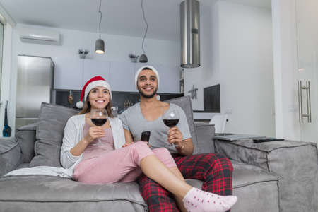 Couple Wearing Santa Hand And Holding Wine Glasses Watch Tv On Christmas Morning Man And Woman Celebrate Holidays Together At Home Stock Photo