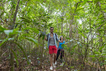 and hiking path: Couple With Backpacks Trekking On Forest Path, Young Man And Woman Holding Hands Walk On Hike Tourists Adventure Activity