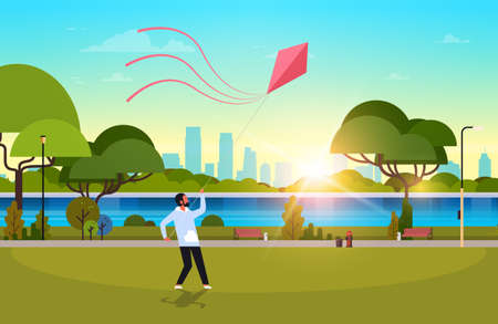 young man launching kite outdoors modern public park guy playing wind toy holiday concept cityscape sunset background horizontal flat vector illustration Illustration