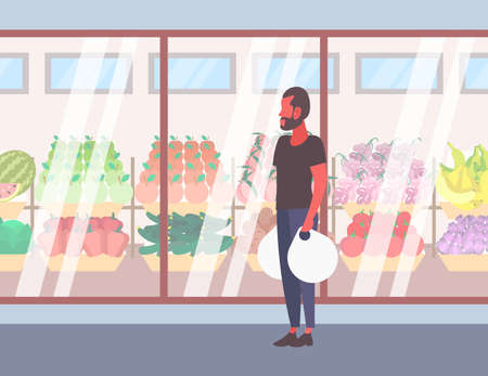 casual man holding shopping bags walking in front of fresh organic fruits vegetables modern supermarket shop glass window guy customer full length cartoon character flat vector illustration