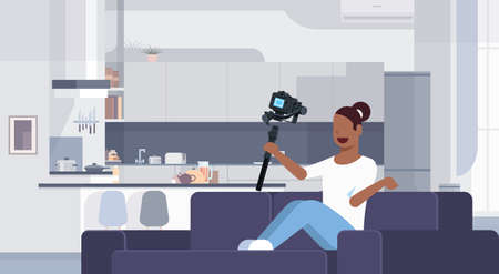 girl blogger recording video on camera african american woman sitting on couch modern kitchen interior using gimbal stabilizer social media blog concept full length flat horizontal vector illustration
