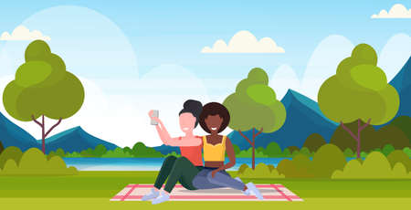 two women taking selfie photo on smartphone camera mix race female characters sitting outdoor on grass posing over nature landscape mountains background flat full length horizontal vector illustration