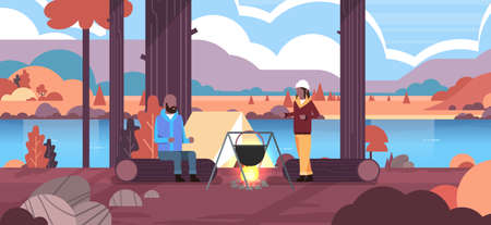 couple hikers african american man woman cooking meals in bowler boiling pot at campfire camp tent camping concept autumn landscape nature river mountains background horizontal vector illustration Ilustrace