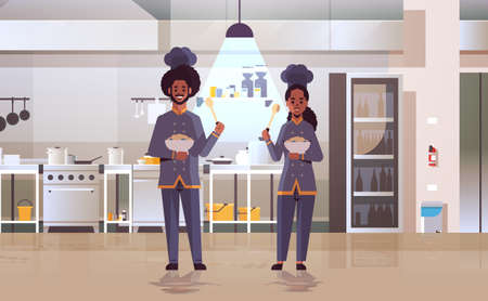 cooks couple professional chefs holding plates with porridge african american workers in uniform tasting dishes cooking food concept modern restaurant kitchen interior flat full length horizontal vector illustration