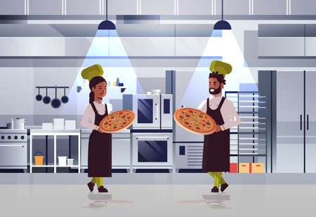 professional chefs couple holding trays with fresh pizza african american man woman in uniform standing together cooking food concept modern restaurant kitchen interior horizontal full length vector illustration
