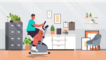 man riding stationary bike at home guy having workout cardio fitness training healthy lifestyle sport