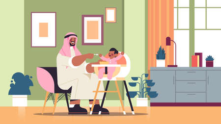 arab father feeding his little son on kids eating chair fatherhood parenting concept dad spending time with baby