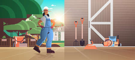girl farmer in uniform with garden and farm tools gardening equipment near wooden barn doors eco farming agriculture