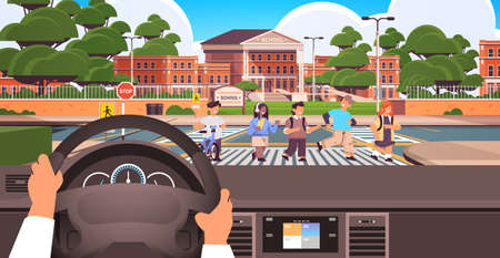 driver holding the steering wheel and waiting schoolchildren crossing road on crosswalk near school building road safety
