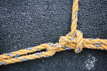 Yellow nylon line tied in a knot on dark background photo