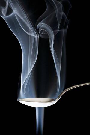 Conceptual abstraction of smoke bending around a silver spoon.