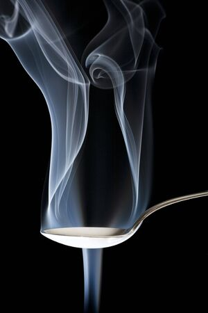 Conceptual abstraction of smoke bending around a silver spoon.