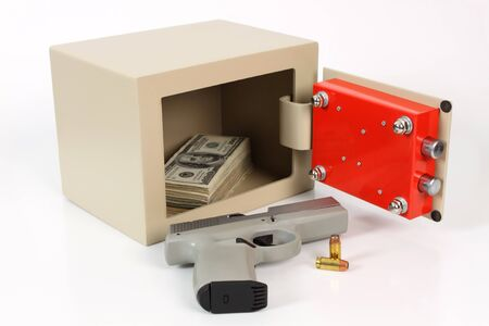 open metal safe with dollars and a pistol on a white background