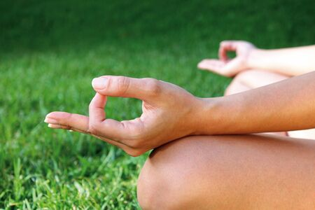 young person meditating on the grass in the garden Stock Photo