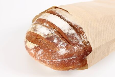 fresh bread in paper bag in the foreground Stock Photo