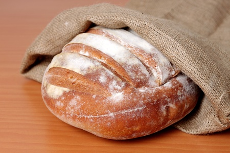 fresh bread in cloth sack on wooden table Stock Photo