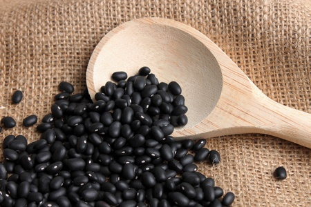 black beans with a wooden spoon on a fabric background